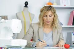 Женщина портрета используя электрическую швейную машину Стоковая Фотография RF