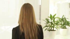 Женщина портрета красивая при длинные волосы смотря в камеру и вращение вокруг Закройте вверх по молодой женщине стороны в студии видеоматериал