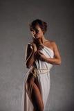 Женщина портрета красивая с элегантной белой предпосылкой стены grunge платья Стоковые Изображения RF
