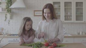 Женщина портрета милая молодая усмехаясь варя салат на таблице, режа цукини Положение маленькой девочки около учить как видеоматериал