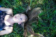 Женщина портрета молодая белокурая кладя в траву при длинные волосы и голубые глазы смотря вверх счастливый стоковые фото