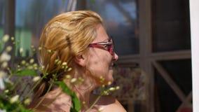 Женщина портрета счастливая в солнечных очках на летнем дне в солнечном цветя саде акции видеоматериалы