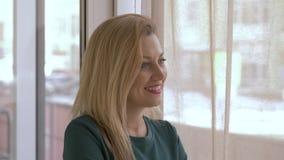 Женщина портрета счастливая смотря вне окно Женщина стороны белокурая усмехаясь и смеясь над видеоматериал