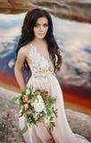 Женщина портрета с голубыми глазами и букетом цветков в ее руках на природе Шикарные волосы и совершенная кожа Стоковые Изображения