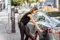 Женщина поручая электрический автомобиль outdoors Стоковое Изображение