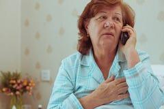 Женщина постаретая больным вызывая ее доктора Стоковая Фотография
