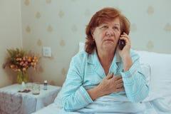 Женщина постаретая больным вызывая ее доктора Стоковое Изображение RF