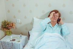 Женщина постаретая больным вызывая ее доктора Стоковое фото RF