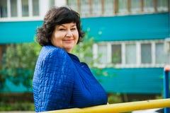 Женщина постаретая серединой среди жилых домов города Стоковая Фотография