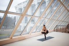Женщина постаретая серединой стоя в одной шагающей тренировке стула, представлении Eka Pada Utkatasana, разрабатывающ, нося sport Стоковые Изображения