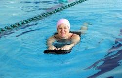 Женщина постаретая серединой в бассейне стоковое изображение