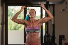 Женщина постаретая серединой изгибая мышцы в спортзале Стоковые Фото