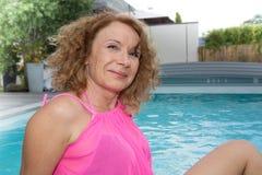 Женщина постаретая серединой дома в ее бассейне стоковое изображение