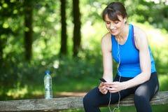 Женщина постаретая серединой ослабляя с mp3 плэйер после тренировки Стоковое Изображение