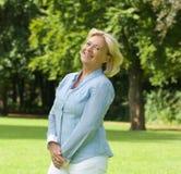 Женщина постаретая серединой усмехаясь outdoors Стоковое Фото