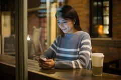 Женщина посылая сообщение на мобильном телефоне в кафе стоковая фотография rf