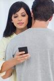 Женщина посылая текстовое сообщение как парень обнимает ее Стоковая Фотография