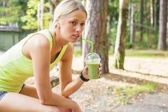 Женщина после smoothie разминки выпивая стоковое фото rf