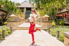 Женщина потехи в красных брюках и высоких пятках стоковое изображение rf