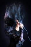 Женщина поя с микрофоном, волосами вверх в воздухе Стоковая Фотография RF