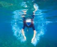 Женщина под водой делает пузыри, женщину шноркеля snorkeling в черной маске Стоковые Изображения RF
