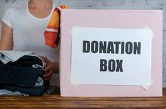 Женщина подготавливает одежды ` s ребенк для пожертвования стоковое фото rf