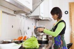 Женщина подготавливая еду на кухне Стоковые Фотографии RF