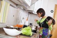 Женщина подготавливая еду на кухне Стоковое Изображение