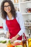 Женщина подготавливая еду салата овощей в кухне Стоковое Фото