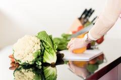 Женщина подготавливая овощи вырезывания еды Стоковая Фотография RF