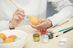 Женщина подготавливая пасхальные яйца Стоковые Фото