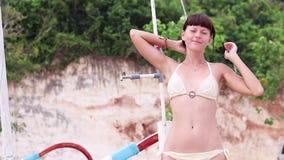 Женщина поливая на пляже тропического острова Бали, Индонезии акции видеоматериалы