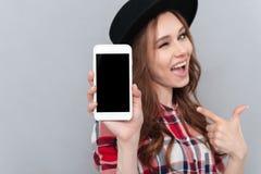 Женщина подмигивая и указывая пальцу на пустой экран мобильного телефона стоковые изображения rf