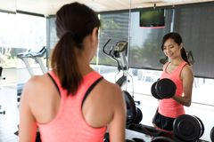Женщина поднимаясь вверх по гантели в спортзале Стоковые Изображения