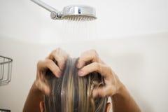 Женщина полоща волосы в ливне Стоковая Фотография