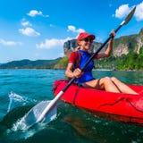 Женщина полощет красный каяк Стоковая Фотография
