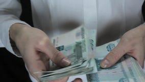 Женщина подсчитывает большое количество денег, русские рублевки акции видеоматериалы