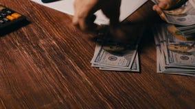 Женщина подсчитывая долларовые банкноты на калькуляторе видеоматериал
