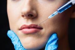 Женщина получая впрыску botox на ее губах Стоковое Фото