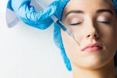 Женщина получая впрыску botox на ее губах Стоковые Фото