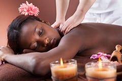 Женщина получая массаж плеча на курорте Стоковые Изображения