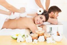 Женщина получая массаж с травяными штемпелями обжатия Стоковая Фотография