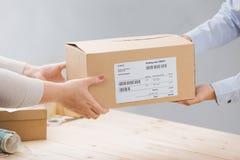 Женщина получая пакет от работника доставляющего покупки на дом стоковое фото