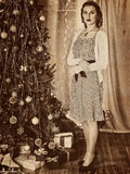 Женщина получая подарки под рождественской елкой Старая бумага желтого цвета фото Стоковое Изображение RF