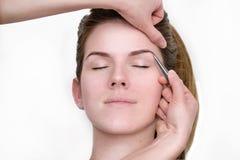Женщина получая tweezing бровь beautician Стоковая Фотография