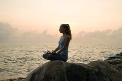 Женщина практикует йогу на зоре, asana на камне, рассвете и изображении девушки, насладиться рассветом, для того чтобы быть счаст Стоковая Фотография
