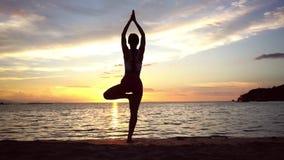 Женщина практикуя представление йоги дерева на пляж на заходе солнца во время летних каникулов видеоматериал