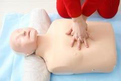 Женщина практикуя CPR на манекене стоковая фотография