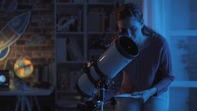 Женщина предаваясь мечтам с профессиональным телескопом стоковое изображение