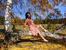 Женщина представляя на дереве березы в лесе осени стоковая фотография